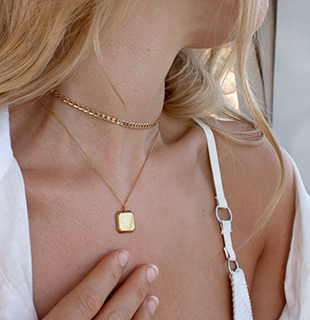 white swimsuit gold necklace